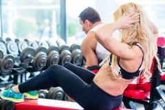 Vänner som lyfter vikter i konditionidrottshall Arkivbild