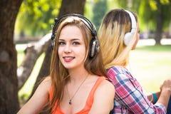 Vänner som lyssnar till musik och, kopplar av parkerar in Lyckliga tonårs- flickor spenderar tid tillsammans i staden Arkivbilder
