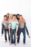 vänner som på ryggen ger sig, rider deras tonåringar Royaltyfri Foto