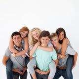 vänner som på ryggen ger sig, rider deras tonåringar Royaltyfri Bild