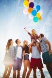 Vänner som poserar med ballongen på sand arkivbilder
