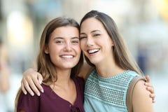 Vänner som poserar med perfekta leenden på gatan Arkivfoto
