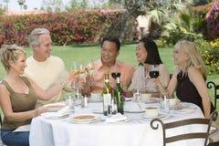Vänner som rostar drinkar på matställetabellen i trädgård Arkivbilder