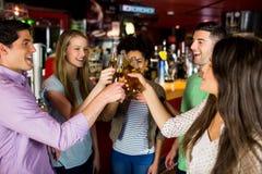 Vänner som rostar med öl fotografering för bildbyråer