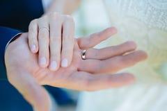 Vänner som rymmer händer med guld- vigselringar bröllop Arkivbilder