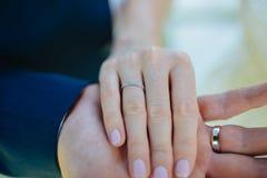 Vänner som rymmer händer med guld- vigselringar bröllop Royaltyfri Foto