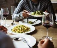 Vänner som samlar äta lycka för mat tillsammans arkivbilder