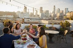 Vänner som samlas på takterrassen för mål med stadshorisont i bakgrund royaltyfri foto