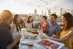 Vänner som samlas på takterrassen för mål med stadshorisont i bakgrund arkivfoto