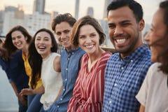 Vänner som samlas på takterrassen för parti med stadshorisont i bakgrund arkivbild