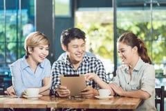 Vänner som ser den digitala minnestavlan i kafét royaltyfria bilder