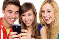 vänner som ser den mobila telefonen Arkivbilder
