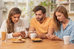 Vänner som sitter i köket och håller ögonen på på deras telefoner royaltyfria bilder
