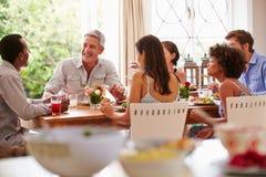 Vänner som sitter på en tabell som talar under ett matställeparti Arkivbild