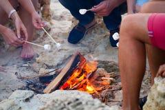 Vänner som sitter på sanden på stranden i cirkel med marshmal arkivbilder