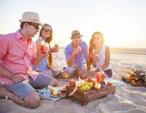 Vänner som sitter på sanden på stranden och dricker lemonad royaltyfri fotografi