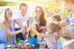 Vänner som sitter på sanden på stranden på sommaren, har picknick royaltyfri foto
