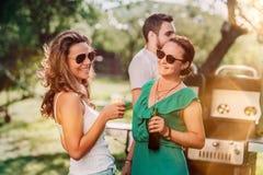 Vänner som skrattar och gör ett grillfestparti med drinkar och gallerhamburgare royaltyfri fotografi