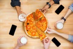 Vänner som smakar pizza och dricker öl på trätabellen arkivbild