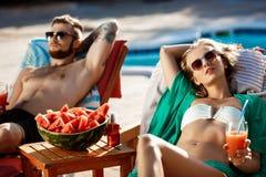 Vänner som solbadar och att dricka coctailar som ligger på chaises, near simbassängen Royaltyfria Foton