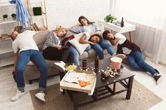 Vänner som sover efter parti i smutsigt rum royaltyfri foto