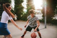 Vänner som spelar basket på domstolen och har gyckel Royaltyfri Bild