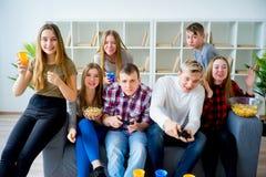 Vänner som spelar en konsollek Fotografering för Bildbyråer