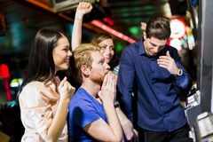 Vänner som spelar i en kasino som spelar springan och olika maskiner fotografering för bildbyråer
