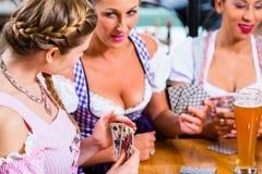 Vänner som spelar kort i gästgivargården eller baren som dricker öl Royaltyfri Foto