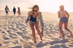 Vänner som spelar lekar på stranden Royaltyfri Bild