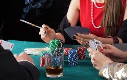 Vänner som spelar pokerleken Fotografering för Bildbyråer