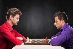 Vänner som spelar schack på svart bakgrund Royaltyfri Fotografi