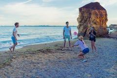 Vänner som spelar volleyboll på en lös strand under solnedgång royaltyfri foto