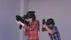 Vänner som spelar VR-skytten, spelar med virtuell verklighetvapen och exponeringsglas Arkivfoto