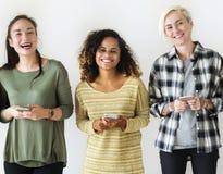 Vänner som står med deras mobiler i hand royaltyfri fotografi