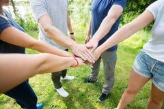 Vänner som staplar händer, medan stå på fält i skog fotografering för bildbyråer