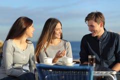 Vänner som talar i en restaurang på stranden Arkivbild