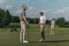 Vänner som talar, medan spela golf tillsammans på gräsplan på dagen arkivbild