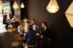 Vänner som talar, medan tycka om nytt kaffe i ett kafé tillsammans Royaltyfri Foto