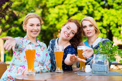 Vänner som talar och dricker i ölträdgård Royaltyfri Foto