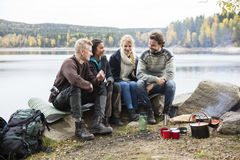 Vänner som talar på Lakeshore under att campa arkivbild