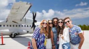 Vänner som tar bilden vid selfiepinnen på flygfält royaltyfri fotografi