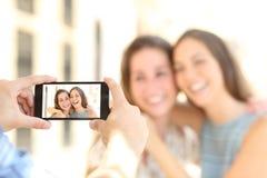 Vänner som tar foto med en smart telefon Arkivfoton