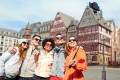 Vänner som tar fotoet vid selfiepinnen i frankfurterkorv arkivfoto