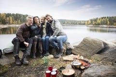 Vänner som tar självståenden på att campa för Lakeside royaltyfri foto