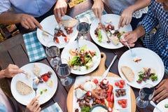 Vänner som tillsammans äter royaltyfria bilder