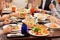Vänner som tillsammans äter middag arkivfoton