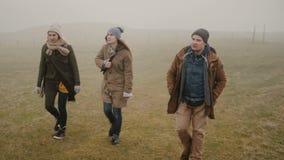 Vänner som tillsammans fotvandrar i dimmig dag Två kvinna och man som tillsammans undersöker Island och att tycka om naturen arkivfilmer