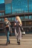 Vänner som tillsammans går Två härliga kvinnor spenderar tid på det hållande kaffet och le för gata royaltyfria bilder