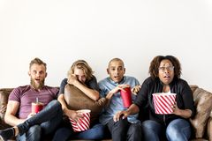 Vänner som tillsammans håller ögonen på filmer inomhus Royaltyfria Bilder